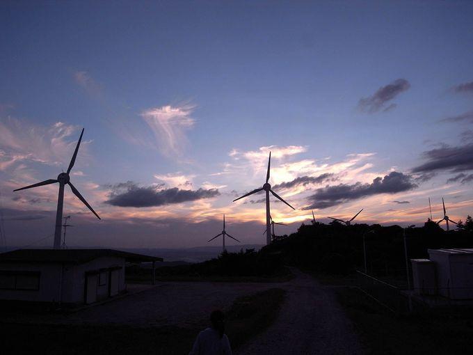 風車のシルエットの脇を駆け抜ける