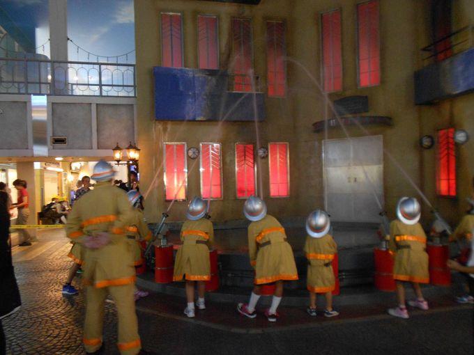 消防隊員出動!消防車に乗って火事現場へ。水をかけて消火作業を体験。