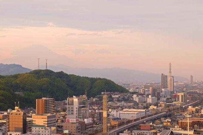 窓に富士山の下、新幹線の上下車両が交差する姿