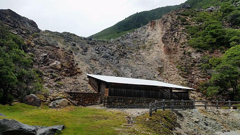 崖に寄り添うワイルドな白屋根の小屋!