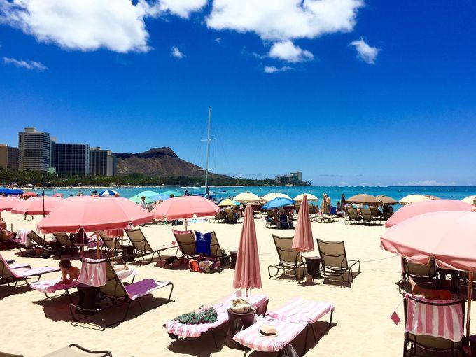 ピンク色のパラソルが広がるビーチ