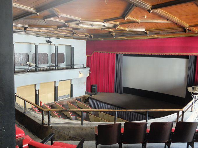 立派な天井。スクリーンの前には舞台。これは本当に映画館?