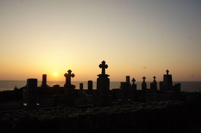 夕陽に浮かぶ十字架の墓標とマリア様の像のシルエット