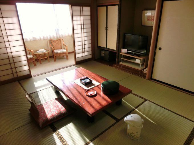 陽光降り注ぐ「ホテル山喜」の客室と南国の窓外
