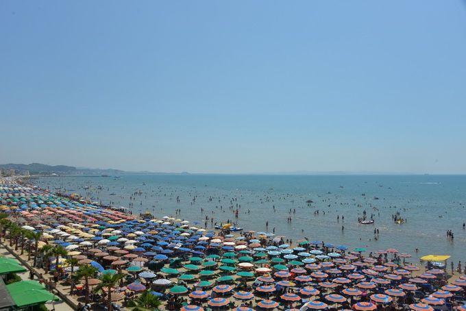 色とりどりのパラソルで覆われる砂浜