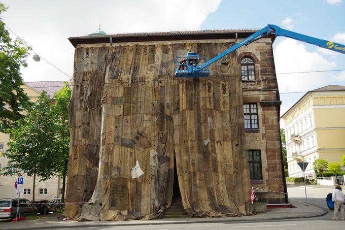 麻袋で覆われるグリム兄弟が住んだ家