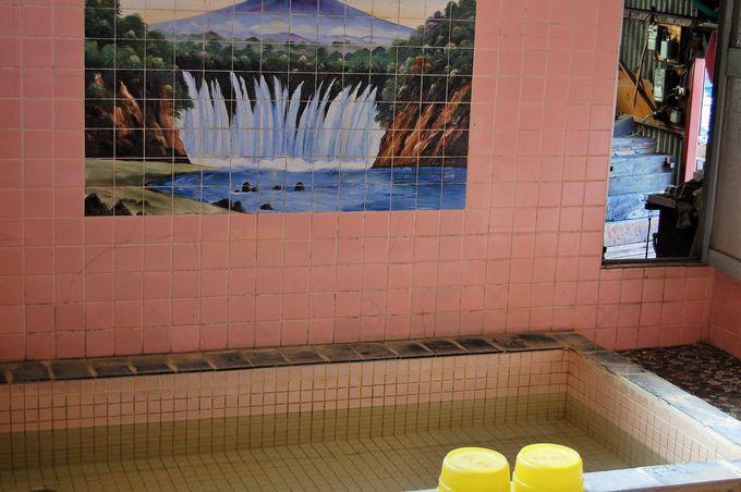壁絵が描かれる素朴な浴室