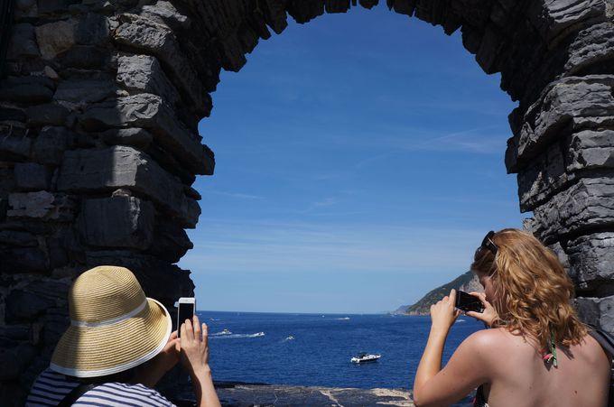 ポルトヴェーネレの縞模様の教会の窓からティレニア海を眺める
